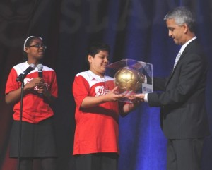 Shayanna Love and Gonzalo Villifan present Sunil Gulati with a soccer ball for his support of America SCORES