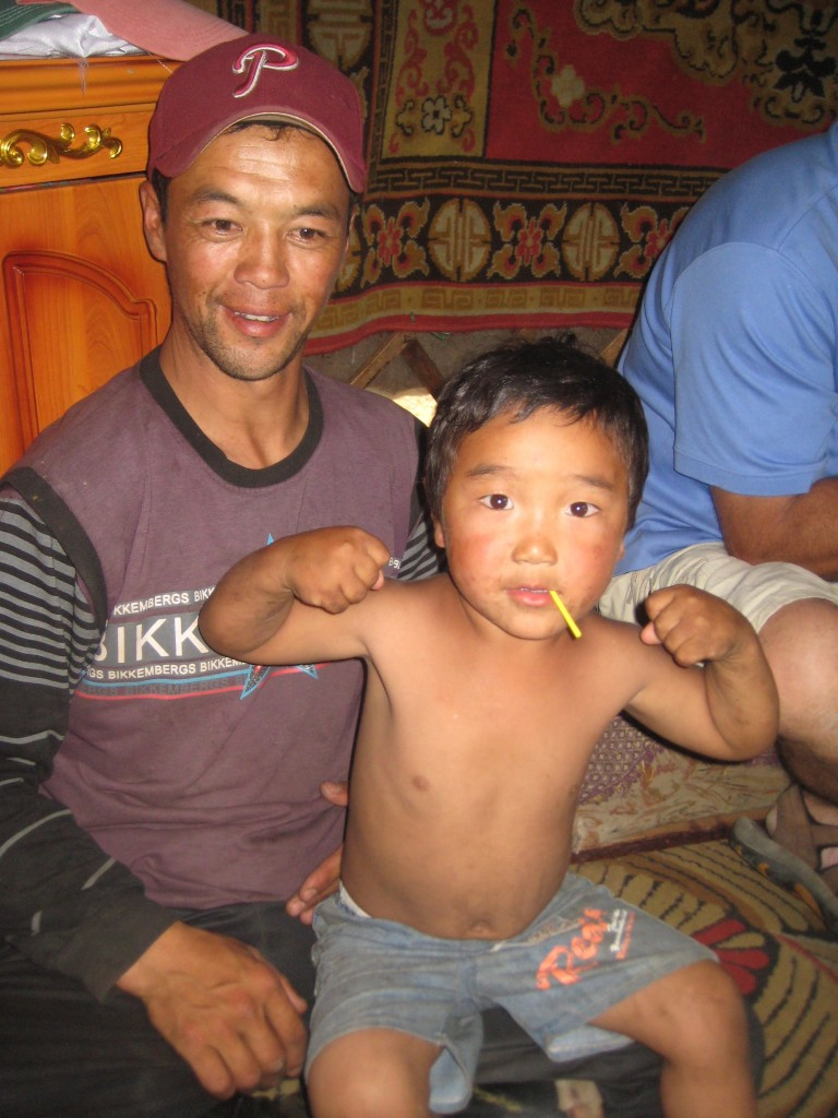 Mongol boy flexes muscles in his ger