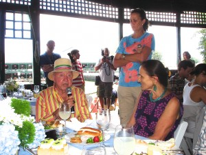 Bud tells tales at a luncheon. Pam Shriver watches and Bud's wife Anita (seated) listens
